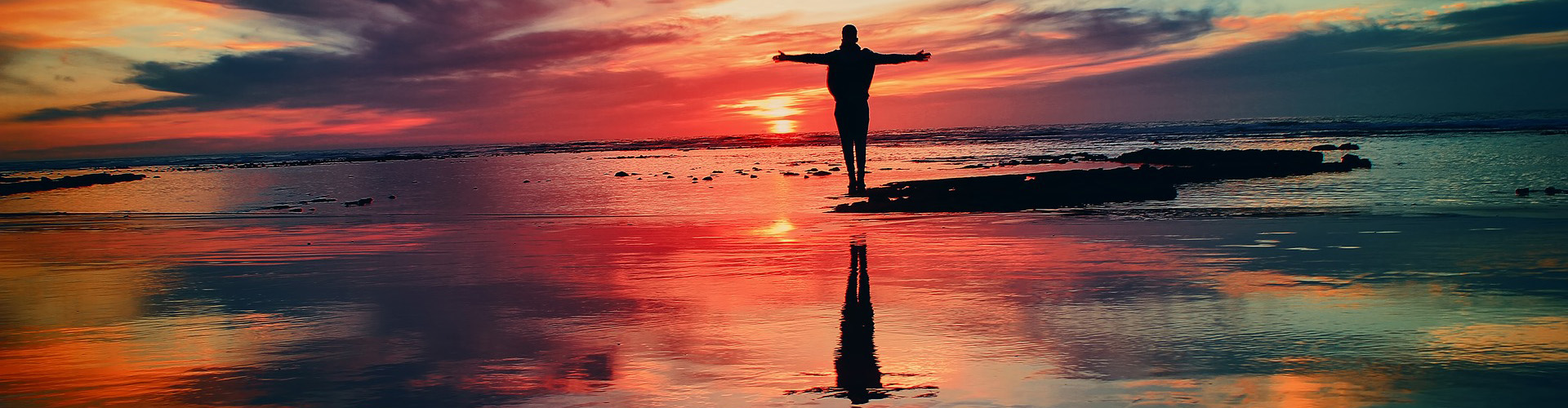 Man standing with his arms open on a beach with a red sunset in the background